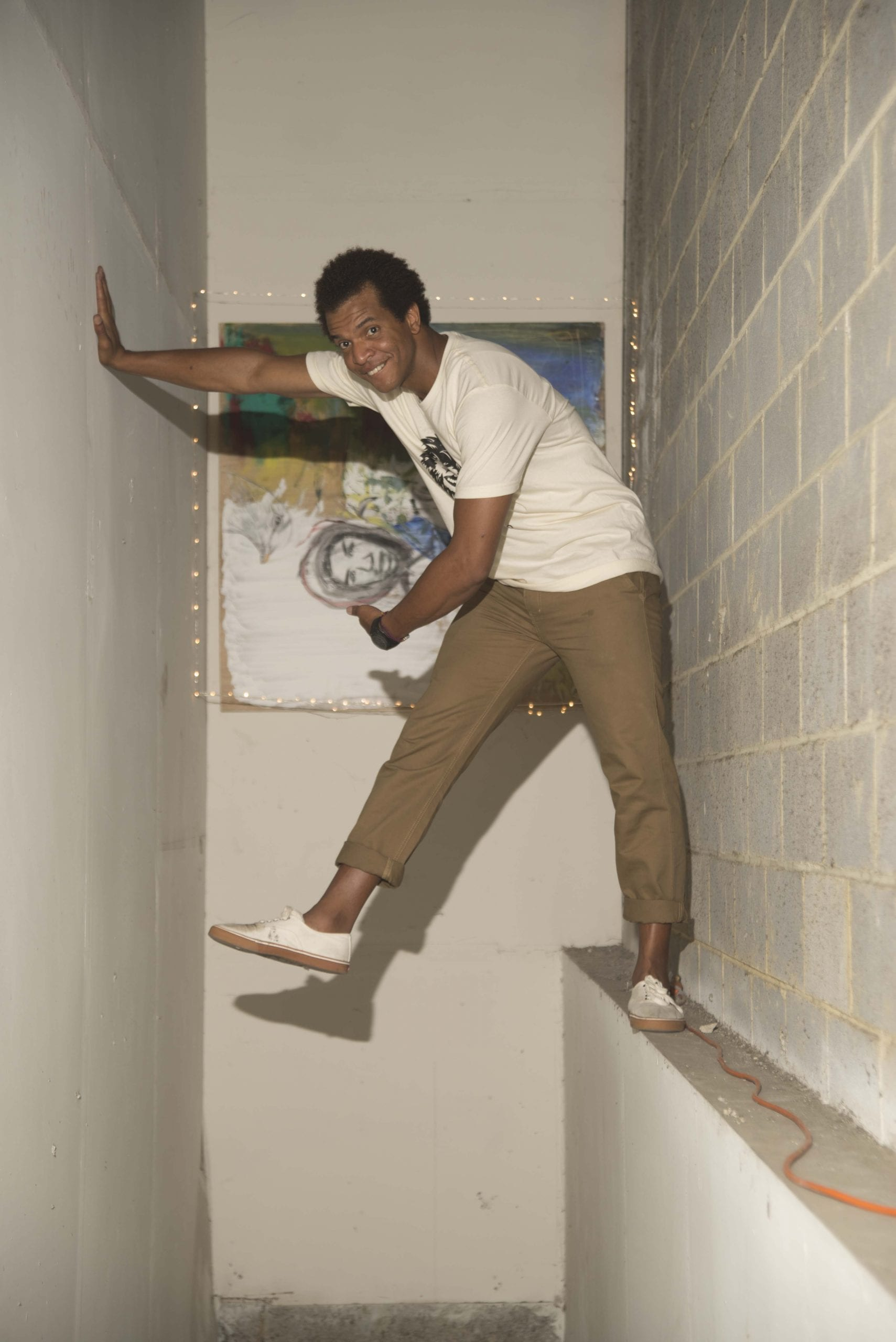 Artist Timoteo Murphy tempted gravity as he mounts one of his many canvases at the warehouse.